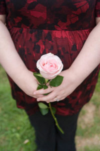 pink rose held by pregnant woman