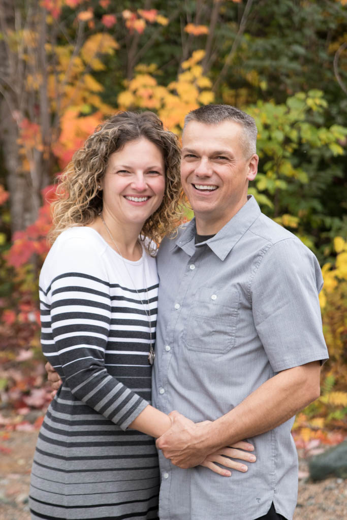 couple in front of fall leaves